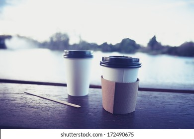 Two paper coffee cups by a lake