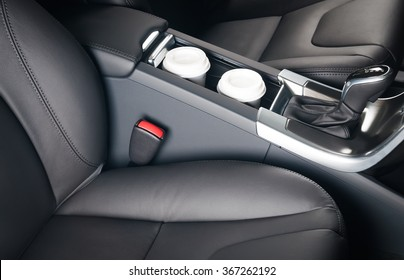 Two paper coffee cups standing inside the car holder between seats
