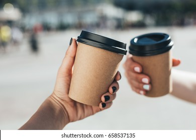 Two paper coffee cups in women's hands with perfect manicure.
