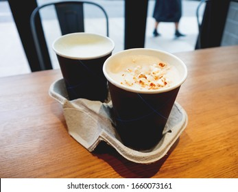Two paper cups with tasty coffee on wooden table in cafe.. Hot beverage with popcorn on frothy milk. Holder made from recycled cardboard for both cups.