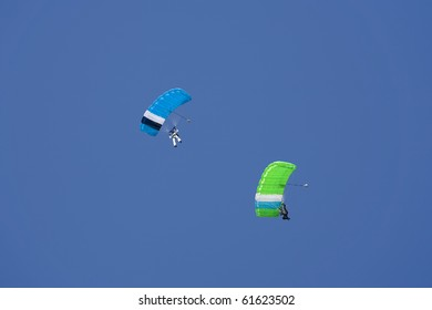 Two parachutists floating in a blue sky