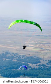 Two paraglider flying over the mountains during a paragliding competition