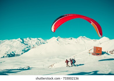 Two paraglider tandem take a run before fly. Colorful parachute. Active lifestyle, Extreme hobbies. Paragliding Georgia. Adventure travel. Winter mountain landscape. Entertainment concept. Adrenalin