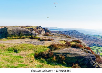 Two paragliders fly over Curbar Edge, in the Derbyshire Peak District, on a hazy spring day.