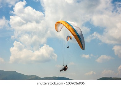 Two paragliders fly over a mountain valley on a sunny summer day. Paragliding in the Carpathians in the summer.