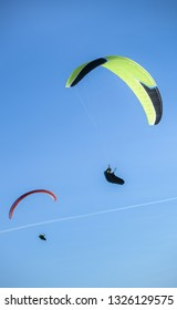 Two paragliders fly paraglides in the blue sky.