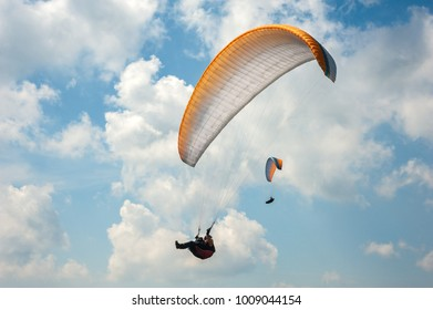 Two paragliders flying in the blue sky against the background of clouds. Paragliding in the sky on a sunny day.