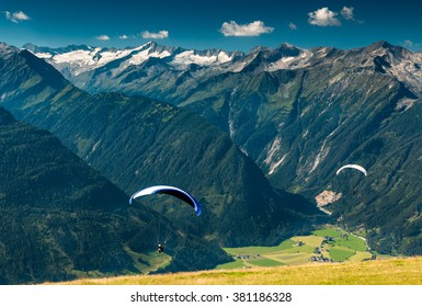 two paragliders flying over the green valley in the mountains with peaks and glacier view in the summer austrian alps near kaprun in salzburg