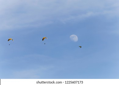 Two paragliders and a hang gliderflying past the moon in the sky Annecy  France
