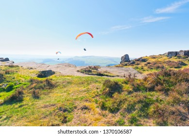 Two paragliders soar over Curbar Edge in the Derbyshire Peak Disrtict on a hazy spring day.