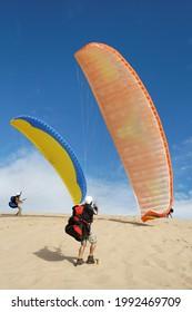 Deux parapentistes utilisant le vent pour monter la dune de sable de Pyla. Sur fond bleu