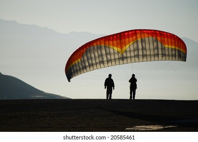 Two paragliders wait for enough wind to launch in the early morning light