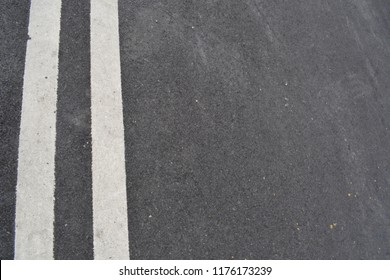 two parallel white paint on the asphalt road using for singage for transporter.