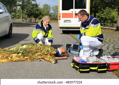 Two paramedics helping a woman after a traffic accident