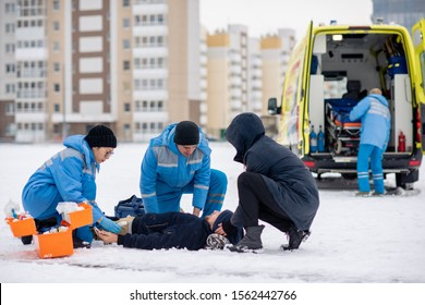 Two paramedics in uniform and guy bending over sick unconscious man lying on snow while giving him first aid outdoors