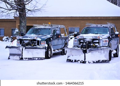 Two parked snowplow trucks backed in to snow packed residential parking lot Large metal chevron shaped plow attachments on commercial vehicles stand ready to answer call for massive snow storm