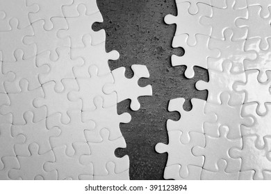 Two parts of white jigsaw puzzle on grey background