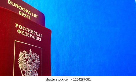 Two passports on the blue textile background. dual citizenship of Estonia and russia. Citizenship of the European Union (EU) and Russian Federation. Top view. Copy space for text or design.