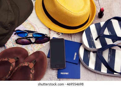 Two passports, sunglasses, hats and map, telephon, lipstick on a grey wooden background
