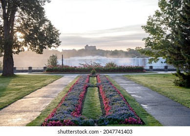 Two pathways with flower gardens between them lead to a view of the American Falls section of Niagara Falls.  View of both Canada in the foreground and the United States in the background.
