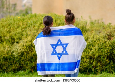 Two patriot jewish teenager girl standing and enjoying with the flag of Israel on nature background.Memorial day-Yom Hazikaron, Patriotic holiday Independence day Israel - Yom Ha'atzmaut concept.