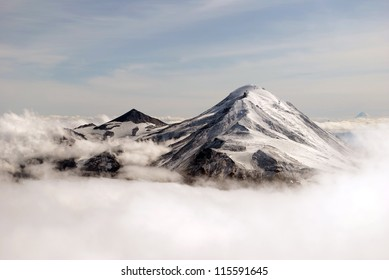 two peaks of volcano covered in snow  in the clouds