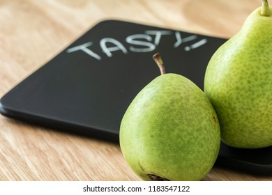 Two pears on a black cutting board with the inscription Tasty. The focus is on the pears.