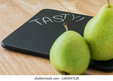 Two pears on a black cutting board with the inscription Tasty. The focus is on the text.