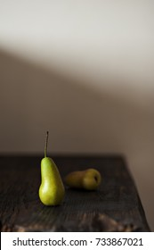 Two pears on a wooden background. Minimal style. Vertical shot. Selective focus.