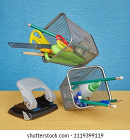 Two pen holders made of metal wire mesh filled with stationery in zero gravity, on blue background.
