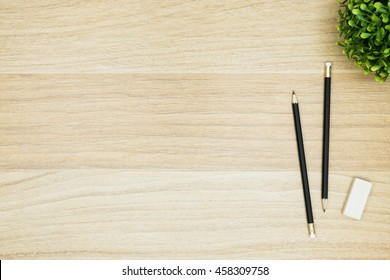 Two pencils with eraser are  on top of wood desk table. Top view with copy space, flat lay.