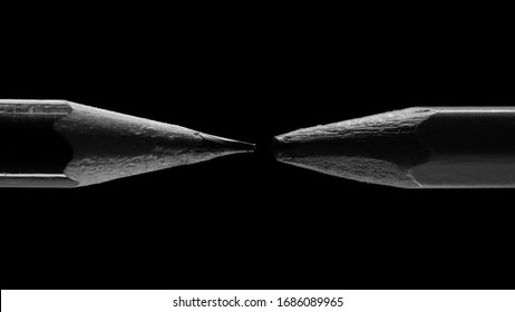 two pencils are isolated on a black background, one pencil is sharp, the other is blunt