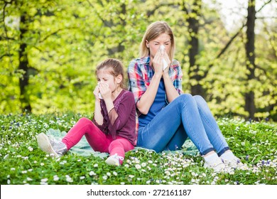Two people with allergy symptom blowing nose