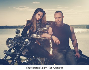 Two people and bike - young woman and bearded man near motorbike. Adventure and vacations concept. VIntage toned image.