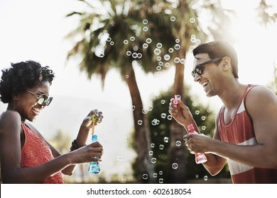 Two people blowing bubbles using bubble wands
