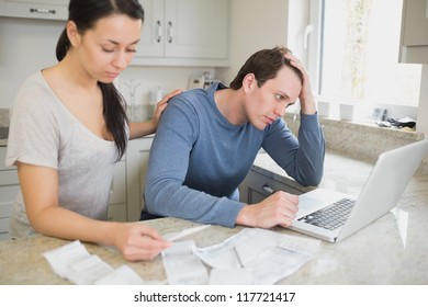 Two people calculating finances and using the laptop