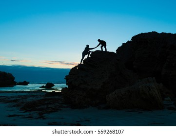 Two people climbing up the cliff teamwork help to success