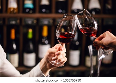 Two people clinking with glasses of red wine, celebrating success or speaking toast in wine restaurant, against racks with wine bottles, close up