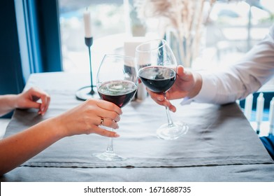 Two people clinking glasses with red wine