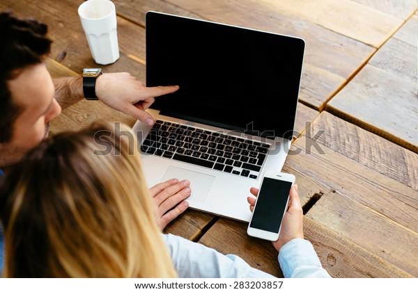 Zwei Personen vergleichen Laptop und Smartphone-Display - Mock up