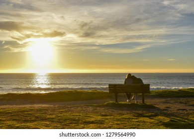 Two people, couple sitting together on the bench on the beach looking at the sunset during the golden hour
