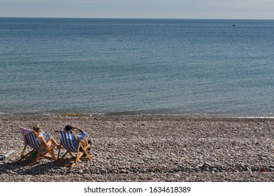 Two people in deckchairs on a beach