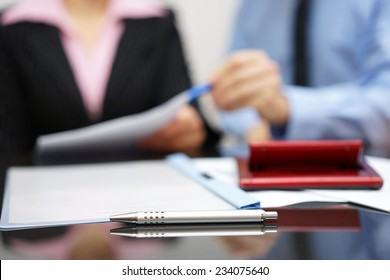 two people discussing about report on business meeting with focus on pen