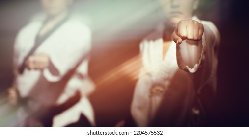 Two people doing taekwondo martial art movement fist, selective focus detail on human hand