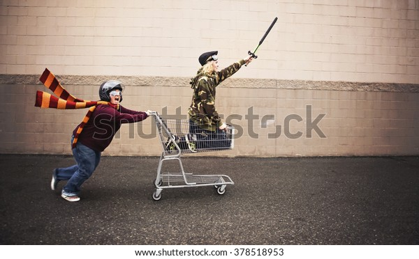 two people dressed up as super heroes or characters horsing around in a shopping cart with goggles and a helmet and sword