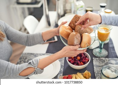 Two people eating breakfast selecting bread rolls of a plate from a variety of crusty white and wholegrain buns in a close up view of their hands