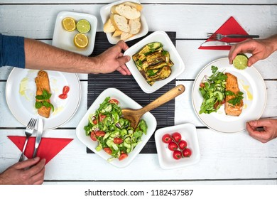Two people eating grilled salmon fish with vegetable salad. Top view on table setting with delicious food on white rustic table.