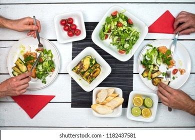 Two people eating salmon fish with vegetable salad. Top view on table setting with delicious food on white rustic table.