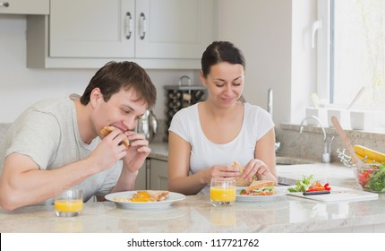 Two people eating sandwiches and drinking juice while sitting in the kitchen