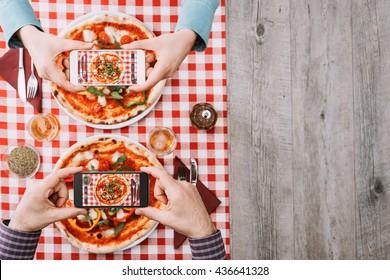 两个人在餐厅吃蔬菜比萨饼,他们用智能手机拍摄食物的照片